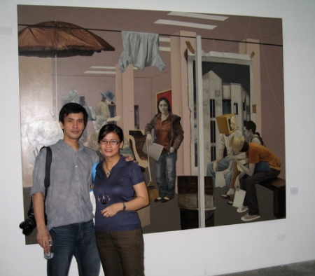 "John and Pam Santos with John's piece, ""Behind the Scenes"""